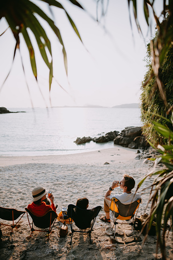 Family sitting on camping chair on beach and enjoying sunset with beer, Okinawa - gettyimageskorea