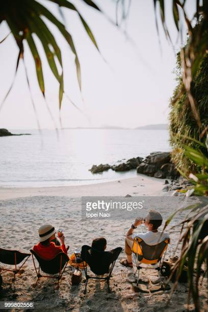 Family sitting on camping chair on beach and enjoying sunset with beer, Okinawa