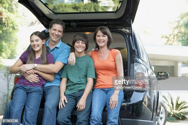 family sitting on car - next to stock pictures, royalty-free photos & images