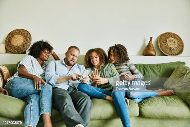 family sitting on couch in living room looking at smart phone - four people stock pictures, royalty-free photos & images