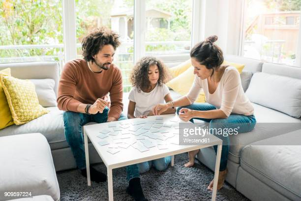 family sitting on couch , playing memory game - board game stock pictures, royalty-free photos & images