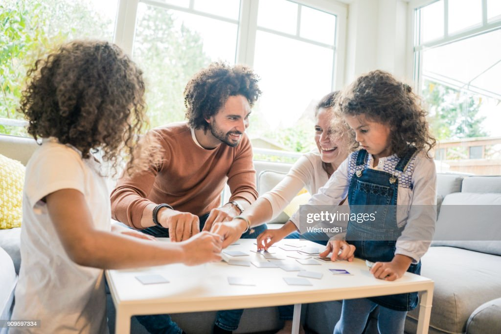 Family sitting on couch , playing memory game : Stock Photo