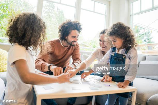 family sitting on couch , playing memory game - leisure games stock pictures, royalty-free photos & images