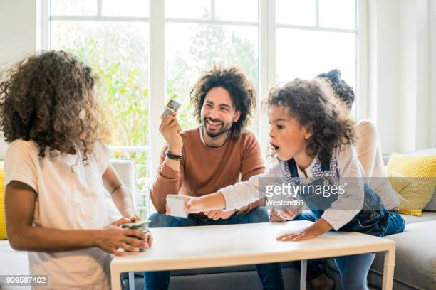 family sitting on couch , playing memory game - game board stock photos and pictures