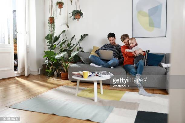 family sitting on couch, using laptop - beide elternteile stock-fotos und bilder