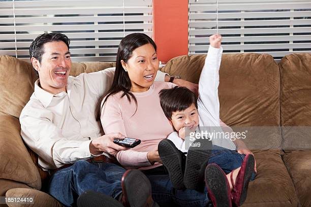 Family sitting on couch watching TV