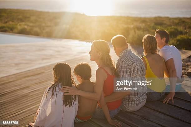 family sitting on deck by swimming pool - niece stock pictures, royalty-free photos & images