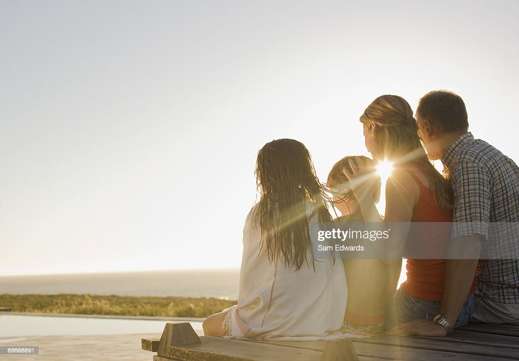 Family sitting on deck in afternoon sun : Stock Photo