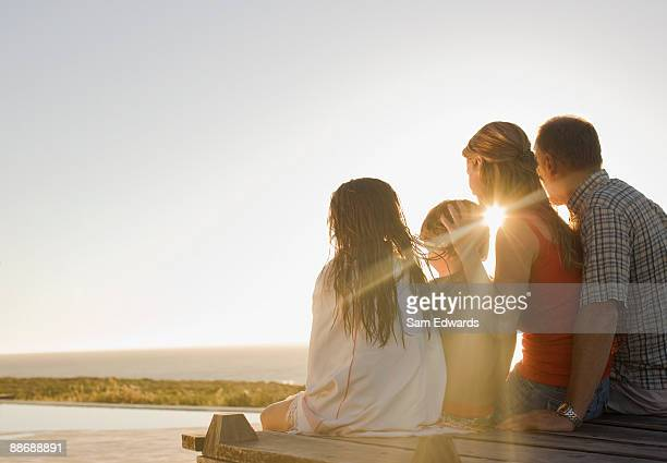 family sitting on deck in afternoon sun - pier stock pictures, royalty-free photos & images