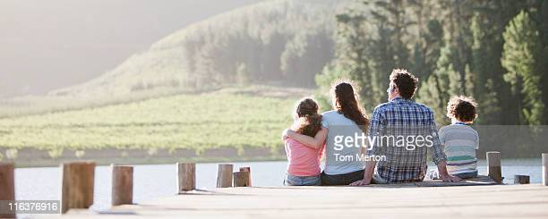 Family sitting on dock by lake