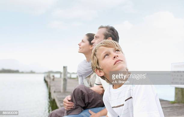 Family sitting on dock near lake