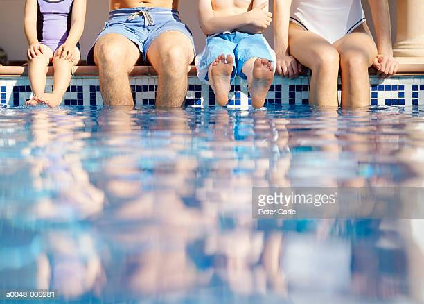 family sitting on edge of pool - zwembroek stockfoto's en -beelden