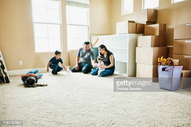 family sitting on floor of living room of new home during move in day - latin american and hispanic stock pictures, royalty-free photos & images