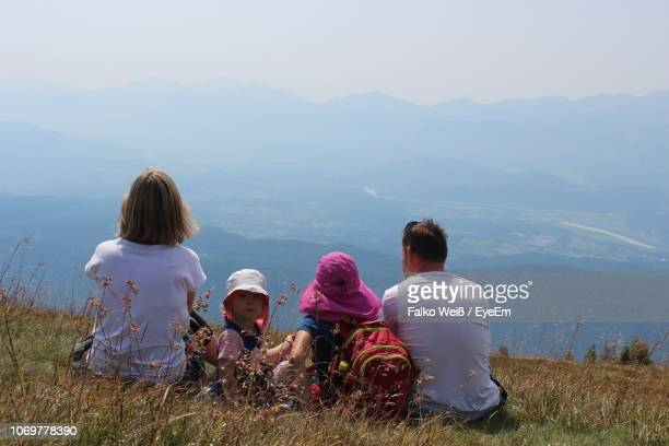 Family Sitting On Mountain Against Sky