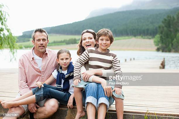 familie sitzt auf dem pier von lake - familie mit zwei kindern stock-fotos und bilder