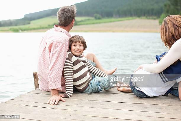 Famille assis sur le quai près du lac