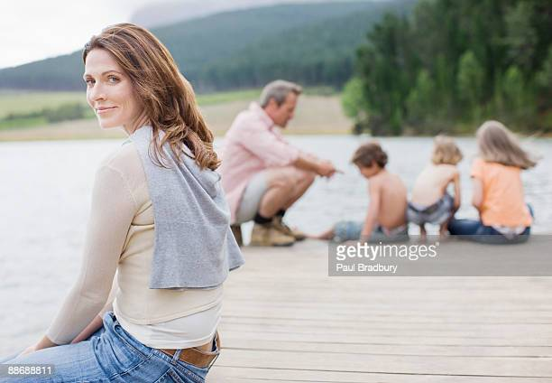 Family sitting on pier by lake