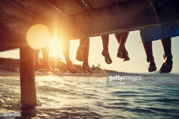 family sitting on pier by the sea - happy family stock photos and pictures