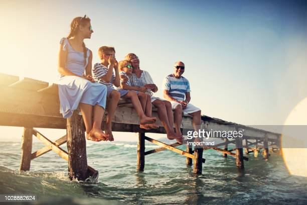 family sitting on pier by the sea - candid beach stock photos and pictures