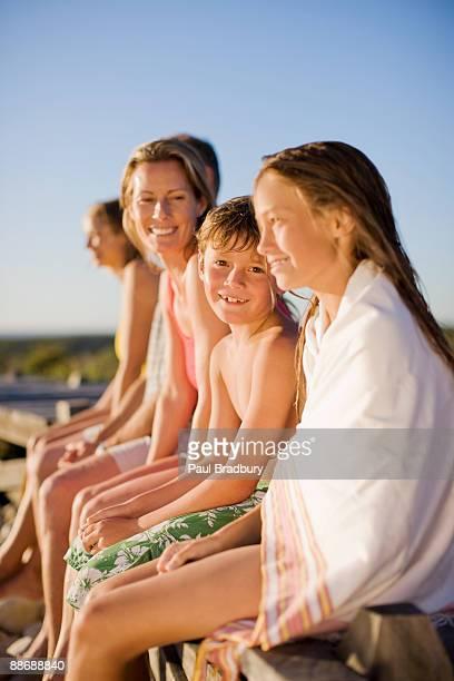 familie sitzt auf dem pier in der nähe von strand - jungen in badehose 12 jahre stock-fotos und bilder