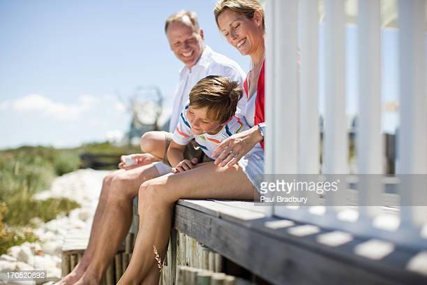 Family sitting on pier near ocean
