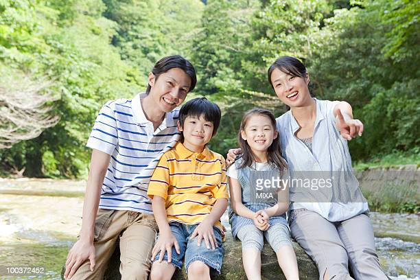 Family Sitting on Rock