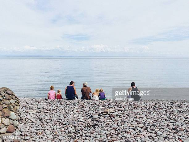 family sitting on rocky beach looking at ocean - ポーロック ストックフォトと画像