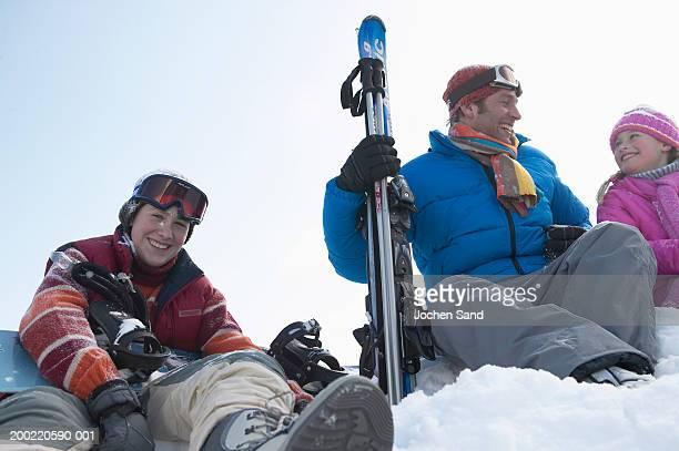 family sitting on ski slope, smiling, portrait - ski pants stock pictures, royalty-free photos & images