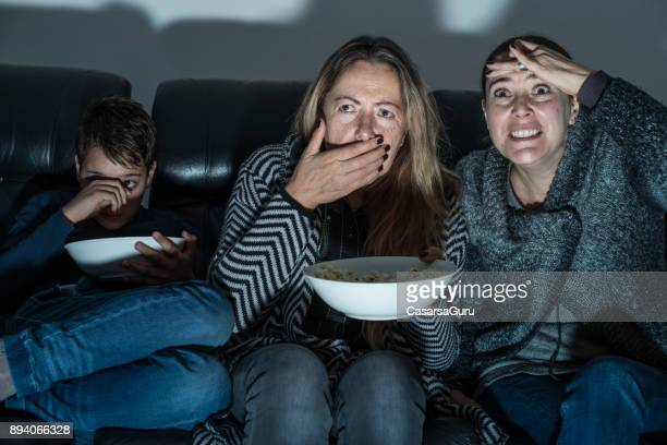 family sitting on sofa and watching tv at night - redoubtable film stock photos and pictures