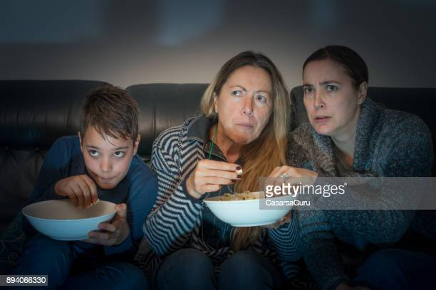 Family Sitting on Sofa and Watching TV at Night