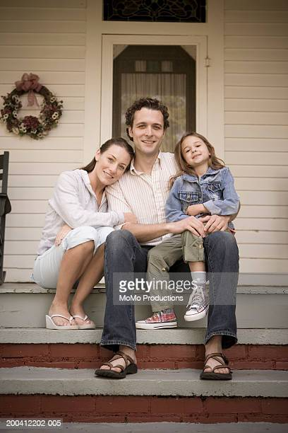 Family sitting on steps in front of house, smiling, portrait