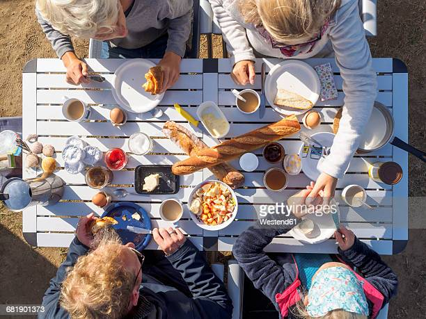 Family sitting on table, breakfast