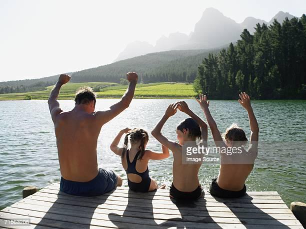 Familie sitzt auf dem Rand einer pier