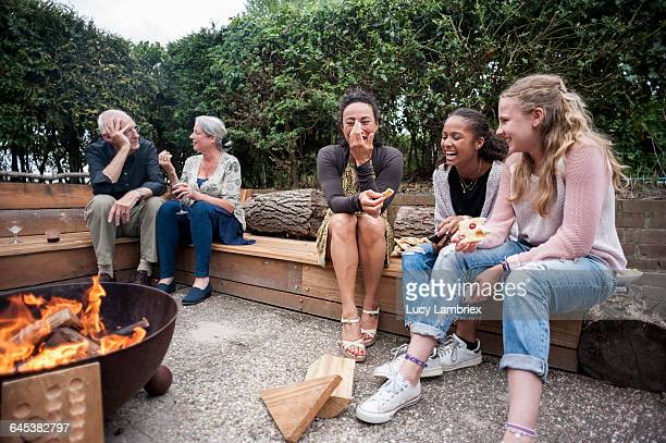 family sitting outdoors by a fire - fire pit stock pictures, royalty-free photos & images