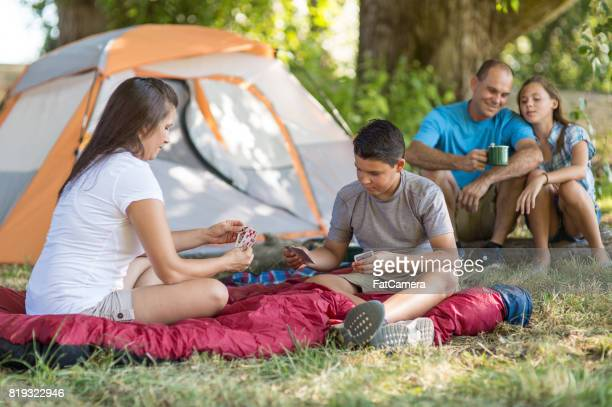 Family sitting outside tent playing cards