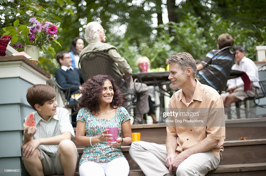 Family sitting together at neighborhood Barbecue : Stock Photo