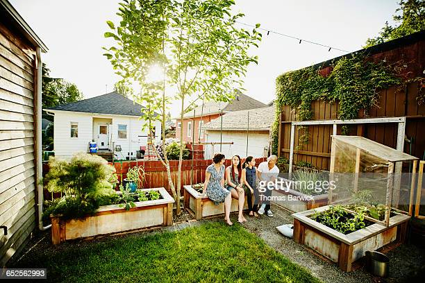 Family sitting together in backyard garden of home