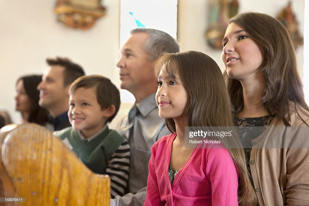 Family sitting together in church : Stock Photo