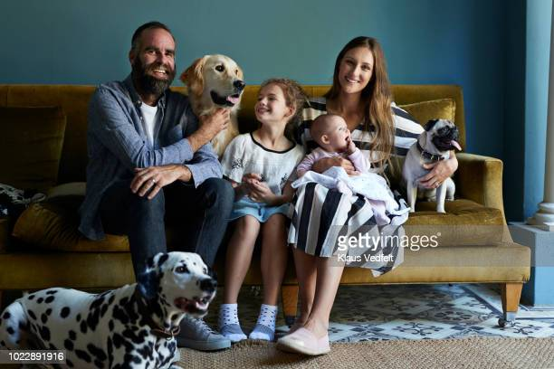 family sitting together in sofa with their dogs - pets stock pictures, royalty-free photos & images