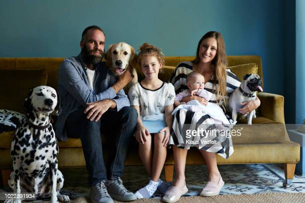 family sitting together in sofa with their dogs - sofa stock-fotos und bilder