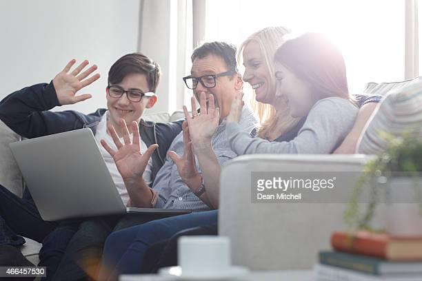 Family sitting together making a video call with digital tablet