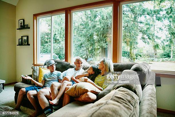 Family sitting together on couch in living room