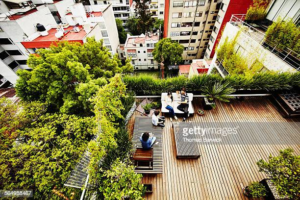family sitting together on rooftop patio of home - city life stock pictures, royalty-free photos & images
