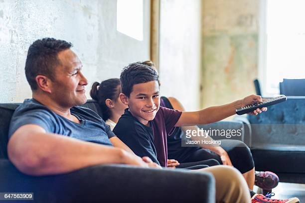 Family sitting together watching tv