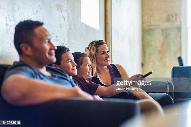 family sitting together watching tv - two parents stock pictures, royalty-free photos & images
