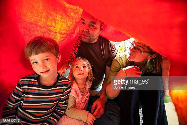 Family sitting under blanket