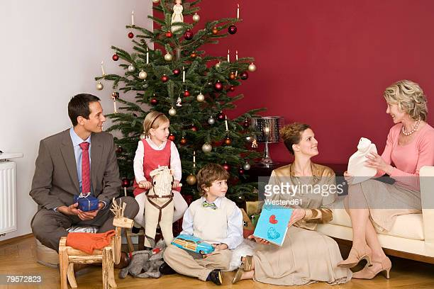 Family sitting under Christmas tree