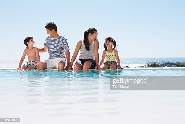 Family sitting with feet in infinity pool