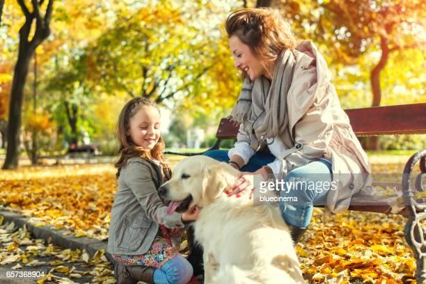Familie zitten met gouden retriever in herfst park