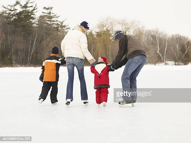 Family skating on frozen lake, rear view